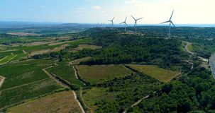 Wind turbines on a hill with fields and vines. Wind turbines on a hill in France in aerial view stock video