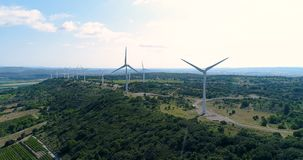 Wind turbines on a hill with fields and vines. Wind turbines on a hill in France in aerial view stock video footage