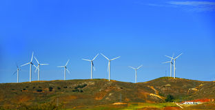 Wind turbines on the hill in front of blue sky Royalty Free Stock Image