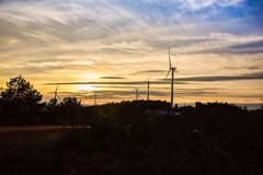 Wind turbines on the hill of a mountain in a beautiful sunset royalty free stock image