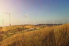 Wind turbines on the hill with sunset. Power energy Stock Photos
