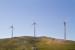 Wind turbines on a hill. Three wind turbines on a hill on the isle of Crete, Greece Royalty Free Stock Photos