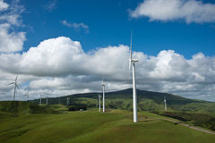 Wind turbines on hills of farmland. Stock Photo
