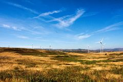 Wind turbines on hilly expanse create energy. Landscape from Portugal, Serra D`Aire. wind power plant clouds dark breeze draught nature ecological ecology stock photography