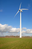 Wind Turbines In The Grass With Blue Cloudy Sky Stock Photo