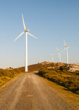 Wind turbines in a landscape with a trail Stock Images