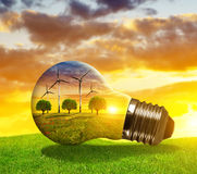 Wind turbines in light bulb at sunset. Stock Image