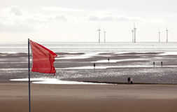 Wind turbines in Mersey. Red flag warns swimmers as wind turbines turn in the ocean off a sandy beach near Liverpool on a cold and cloudy day Royalty Free Stock Images