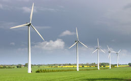 Wind turbines, modern windmills. Wind farm. Modern windmills or wind turbines in the countryside. dark blue skies and green field royalty free stock image