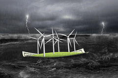Wind turbines on money boat in dark with storm Stock Image