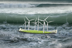 Wind turbines on money boat with oncoming wave in ocean Royalty Free Stock Photo