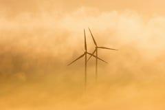 Wind turbines in morning light fog Stock Photos