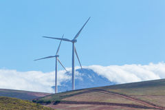Wind turbines with mountains and clouds in the background Royalty Free Stock Photography