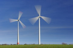Wind turbines in movement. Two wind turbines in movement against blue sky Stock Photo