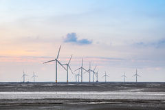 Wind turbines in mud flat Stock Photography