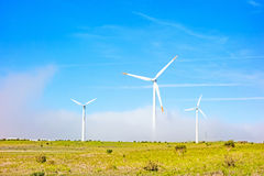 Wind turbines in natural green landscape - blue sky Stock Image