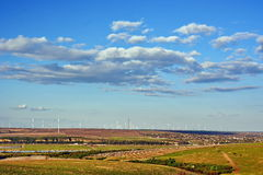 Wind turbines near city Stock Photography