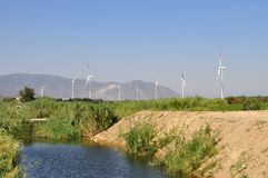 Wind turbines near creek Stock Photos