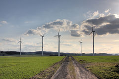 Wind turbines near a dirt road Royalty Free Stock Photos