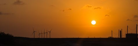 Wind turbines at orange sunset in the rural of Corpus Christi, Texas, USA. Silhouette of wind turbines and power line at orange sunset in the rural of Corpus Stock Images