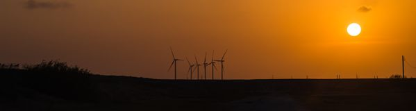 Wind turbines at orange sunset in the rural of Corpus Christi, Texas, USA. Silhouette of wind turbines and power line at orange sunset in the rural of Corpus Stock Photos