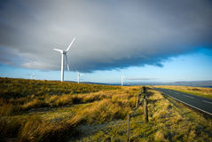 Wind turbines over the blue clouded sky. Wind turbines on the green grass over the blue clouded sky Stock Photos