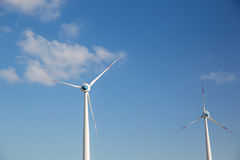 Wind turbines over blue sky. Renewable energy, technology and power concept - wind turbines over blue sky Royalty Free Stock Photography