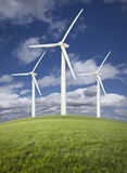 Wind Turbines Over Grass Field and Cloudy Blue Sky Royalty Free Stock Photos