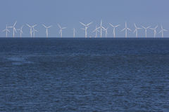 Wind turbines over the sea. A view of several eolic generators standing over the horizon line on the sea Stock Photography