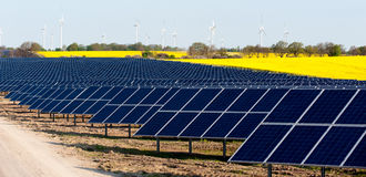Wind turbines and photovoltaic plant. With rape field Stock Photo