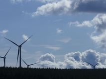 Wind turbines power. Four large powerful  wind turbines set in lush green forest on top of the Rhicos mountains in the rhondda valleys south wales UK. with Royalty Free Stock Images