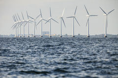 Wind turbines power generator farm along coast sea Stock Photos