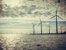 Wind turbines power generator farm along coast sea Stock Photography