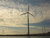 Wind turbines power generator farm in sea. Wind turbines power generator farm for renewable energy production along coast baltic sea near Denmark at sunset / Royalty Free Stock Image