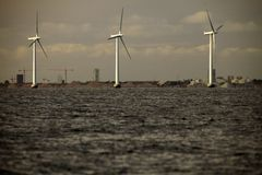 Wind turbines power generator farm in sea. Wind turbines power generator farm for renewable energy production along coast baltic sea near Denmark. Alternative Stock Photos
