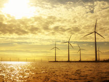 Wind turbines power generator farm in sea. Wind turbines power generator farm for renewable energy production along coast baltic sea near Denmark at sunset / Stock Photo