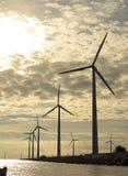 Wind turbines power generator farm in sea. Wind turbines power generator farm for renewable energy production along coast baltic sea near Denmark at sunset / Royalty Free Stock Images