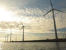 Wind turbines power generator farm in sea. Wind turbines power generator farm for renewable energy production along coast baltic sea near Denmark at sunset / Royalty Free Stock Photos