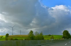 Wind Turbines Power Landscape Highway. A group of wind turbines in agricultural landscape. Photo was taken true the car window on the highway from Vienna to Stock Images