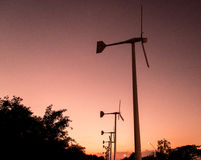 Wind turbines with power line on the sunset Stock Images