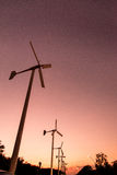 Wind turbines with power line on the sunset Stock Photography