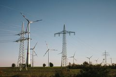 Wind turbines and power lines on a field stock photos