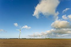 Wind turbines of a power plant for electricity generation in Normandy, France. Concept of renewable sources of energy. Agricultural fields. Environmentally Royalty Free Stock Photo