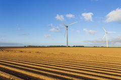 Wind turbines of a power plant for electricity generation in Normandy, France. Concept of renewable sources of energy. Agricultural fields. Environmentally Stock Images