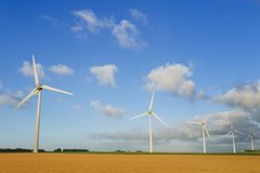 Wind turbines of a power plant for electricity generation in Normandy, France. Concept of renewable sources of energy. Agricultural fields. Environmentally Stock Photography