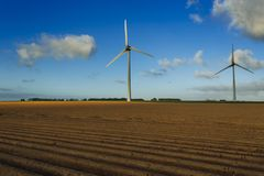 Wind turbines of a power plant for electricity generation in Normandy, France. Concept of renewable sources of energy. Agricultural fields. Environmentally Royalty Free Stock Photos