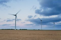 Wind turbines of a power plant for electricity generation in Normandy, France. Concept of renewable sources of energy. Agricultural fields. Environmentally Royalty Free Stock Images