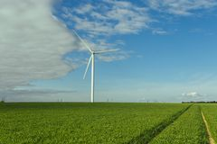Wind turbines of a power plant for electricity generation in Normandy, France. Concept of renewable sources of energy. Country sunny landscape. Environmentally Royalty Free Stock Image