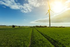 Wind turbines of a power plant for electricity generation in Normandy, France. Concept of renewable sources of energy. Country sunny landscape. Environmentally Stock Image