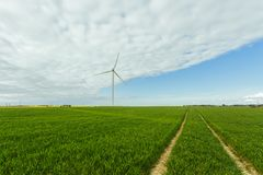 Wind turbines of a power plant for electricity generation in Normandy, France. Concept of renewable sources of energy. Country sunny landscape. Environmentally Stock Photography